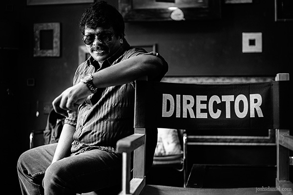 Black and white portrait of actor-director Parthiban Radhakrishnan sitting next to a director's chair