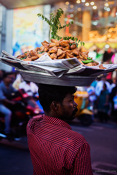 A samosa seller crossing the road in T. Nagar in Chennai