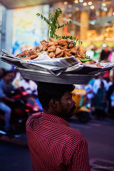 A samosa seller crossing the road in T. Nagar in Chennai