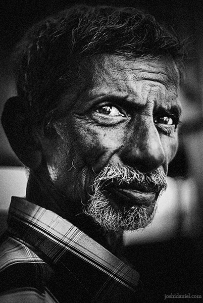 Black and white portrait of an old man at Marina Beach, Chennai with a furrowed look