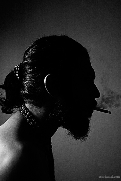 Black and white portrait of Abilash Thankan smoking in darkness