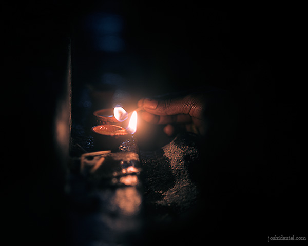 A woman lighting oil lamps during the Karthikai Deepam festival in Kapaleeshwarar Temple in Chennai