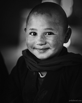 Black and white portrait of a smiling young Buddhist monk in a Monastic school in Hemis, Ladakh