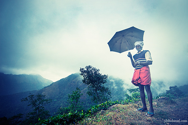 Old man standing on Ponmudi hills, holding an umbrella