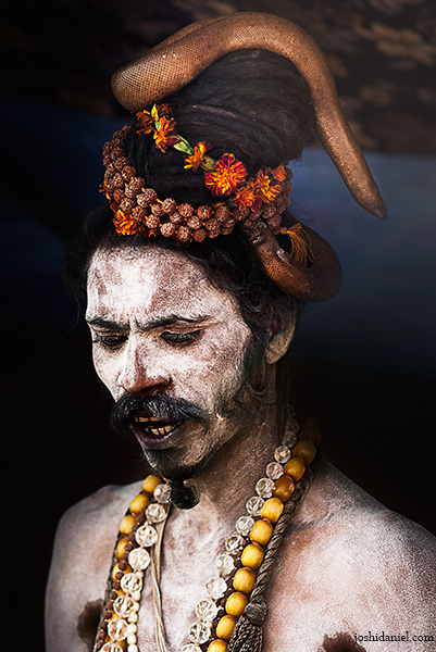 Naga Sadhu with a two-headed snake wrapped around his head in Varanasi