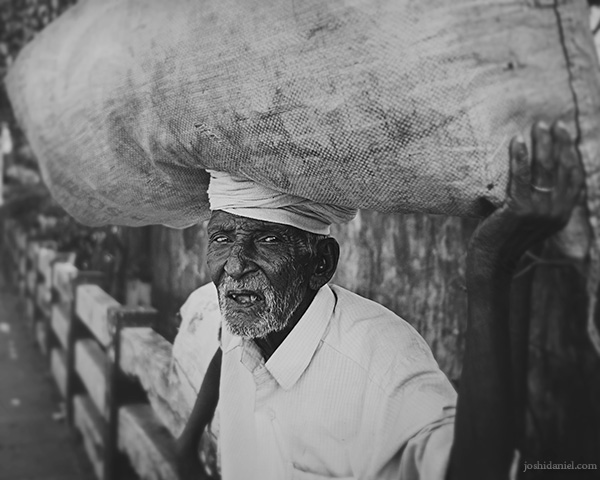 Old man in Trivandrum carrying a big load on his head