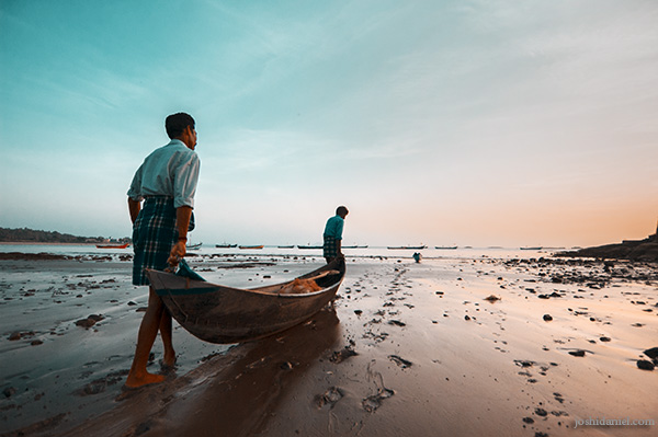 Fishermen in Murudeshwara, Karnataka carrying their boat into the sea after sunset