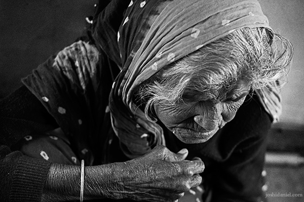 Black and white portrait of an old woman sitting inside a train in Haridwar