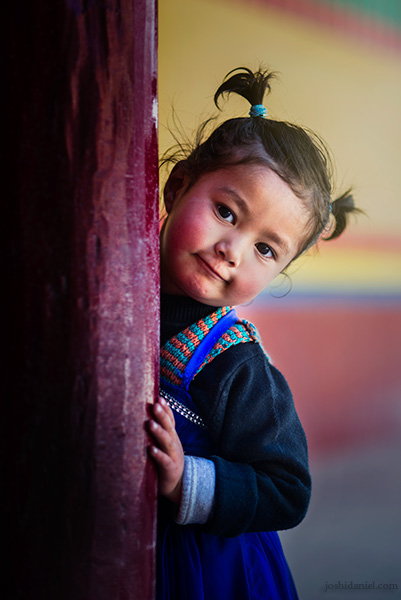 Portrait of a cute young girl in Hemis Monastery, Ladakh, peeking from behind a pillar