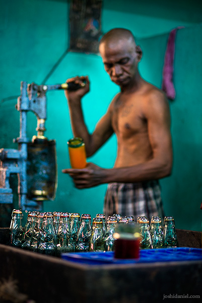A worker at Vasu and Co. Goli soda factory in Chennai aerating the contents of a soda bottle