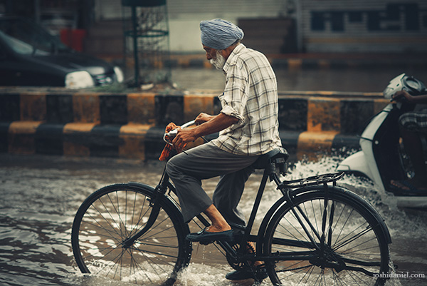 A turbaned old man cycling away on a flooded road during the rains in Amritsar, Punjab