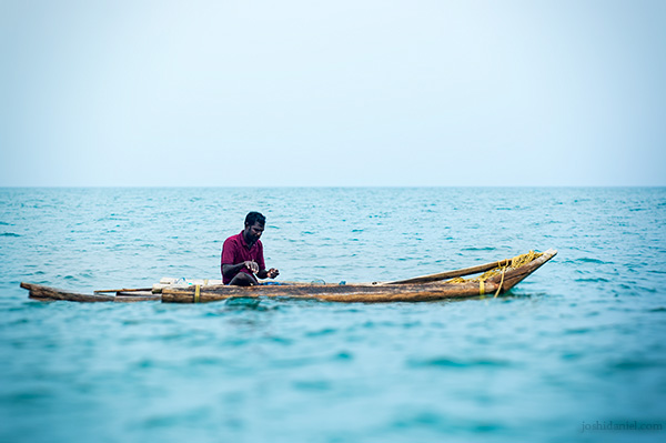 A fisherman fishing from his catamaran in the middle of the sea in Tamil Nadu, India