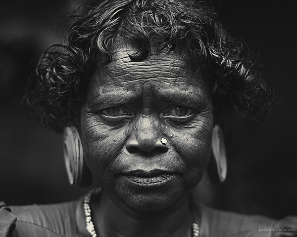 Black and white portrait of a Paniya woman with a large ear plug from Wayanad, Kerala