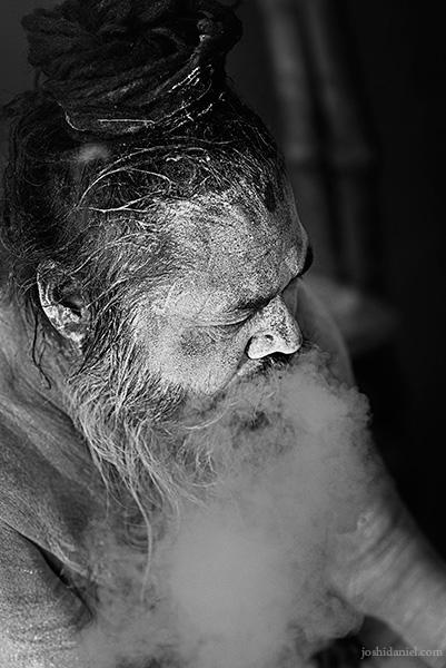 Black and white portrait of a Naga sadhu smoking in Varanasi