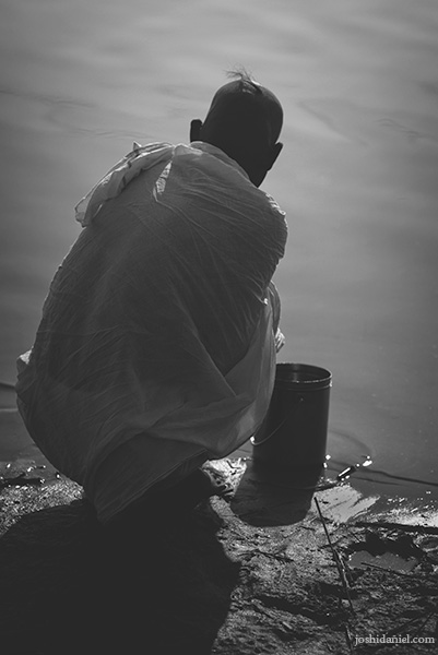 A pilgrim sitting by the river side at the Maha Kumbh Mela in Allahabad