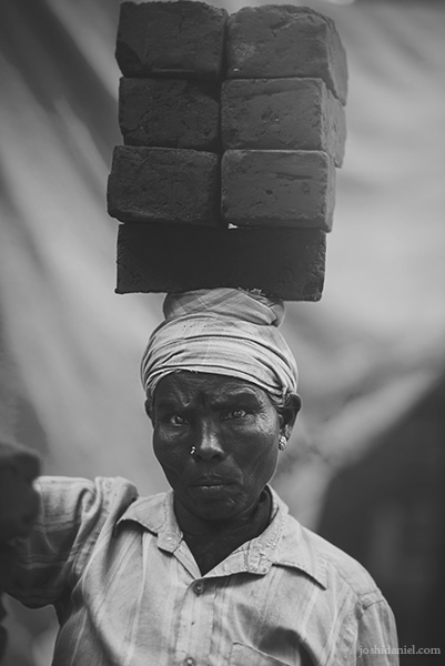 Black and white portrait of a female labourer in Chennai, India, carrying a large set of bricks on her head