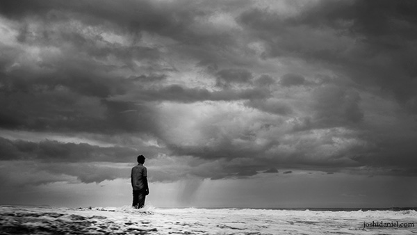 Black and white photo of a man standing in the sea while rain clouds gather above him in Trivandrum, Kerala