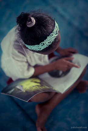 Little girl reading a story book in Taman Bacaan Pelangi (Rainbow Reading Gardens) in Melo Village in Flores, Indonesia