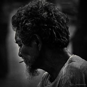 Black and white portrait of a banana vendor smoking in Grant Road, Mumbai
