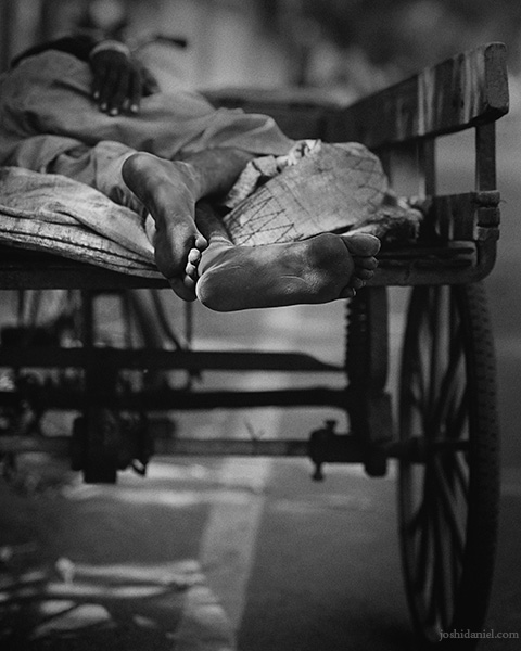 Black and white photo of the feet of a man sleeping on a pushcart in Chennai, India