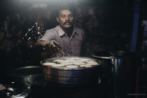 Portrait of an idli vendor splashing water over cooked idlis in Chennai