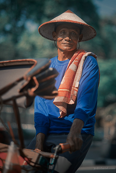 Portrait of a smiling becak (rickshaw) driver wearing a straw hat in Yogyakarta, Indonesia