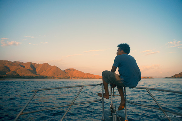 Man sitting on the bow of a boat sailing from Pink Beach, Indonesia