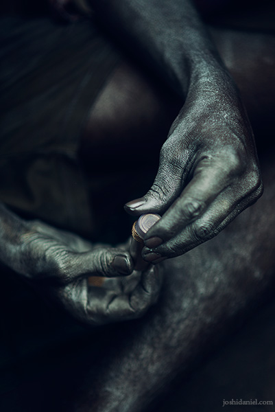 Metallic silver-coated hands of a boy selling colours during the Holi festival in Sowcarpet in Chennai