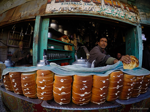 A tea seller standing behind a full stack of buttered bread in a tea shop in Kokernag, Jammu and Kashmir