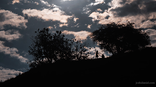 Silhouette of a girl dancing on top of a hillock by Pink Beach in Indonesia