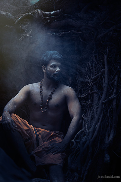 Portrait of Vivek Gopan sitting next to an uprooted tree in Kallar, Trivandrum