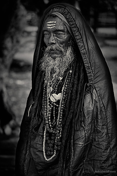 Black and white portrait of a man in a sleeping bag during Kumbh mela, Haridwar
