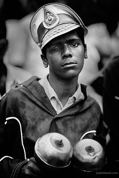 A black and white portrait of a young boy from a Chennai musical band holding a pair of maracas