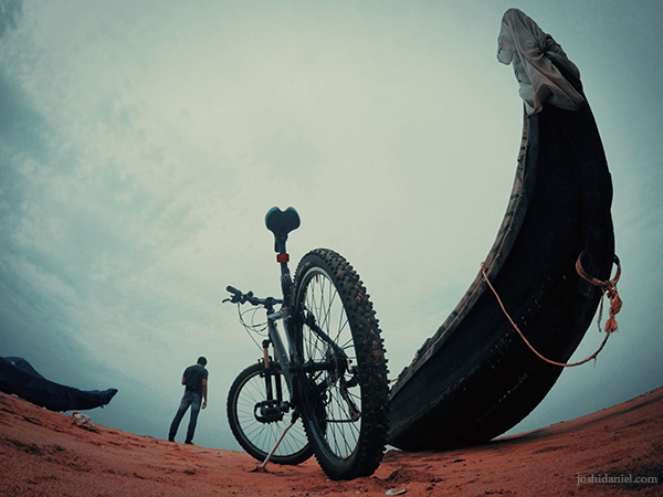 Self-portrait of joshi daniel standing next to a bicycle and a boat at Shankhumugham beach in Trivandrum