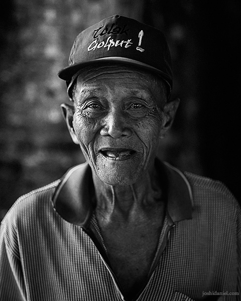 Black and white portrait of a smiling old man at the Banyan tree temple at Senggarang Village, Indonesia