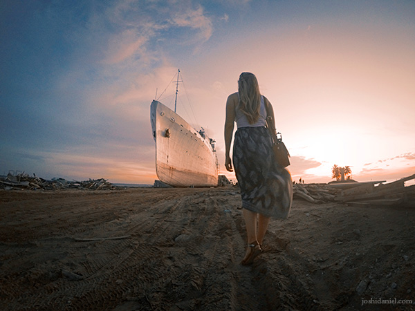Phoebe Lee walking towards a ship anchored at Bintan Island in Indonesia during sunset
