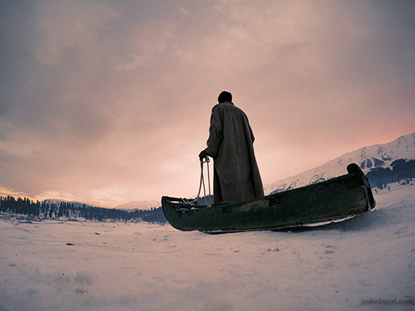 A Kashmiri sled puller holding the reins of the sled on a snowy evening in Gulmarg