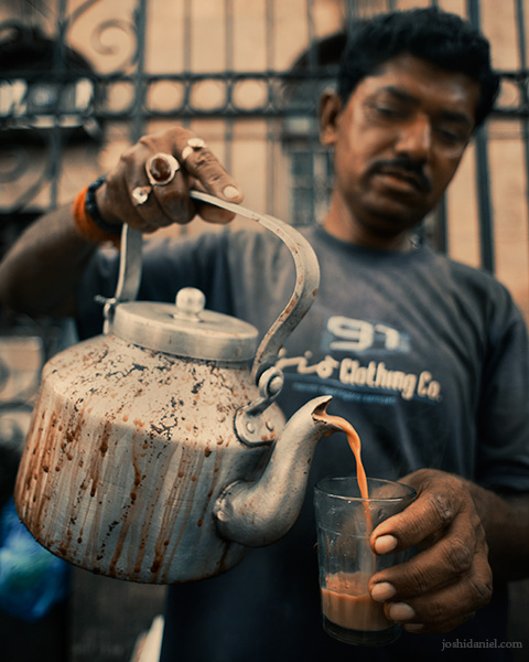 A roadside tea seller in Mumbai serving cutting chai from a kettle