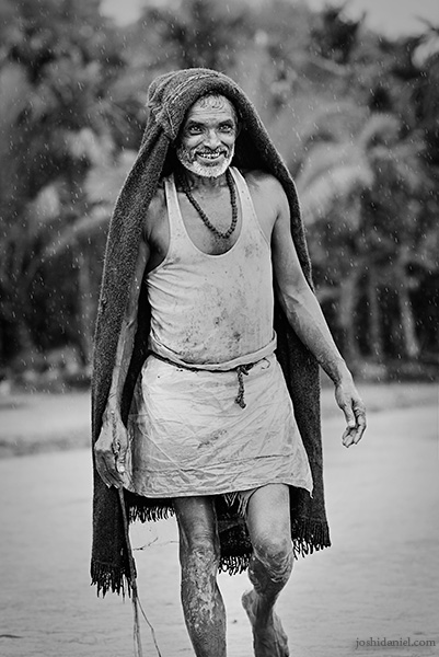 A smiling farmer in Karnataka, India shielding himself from the rain