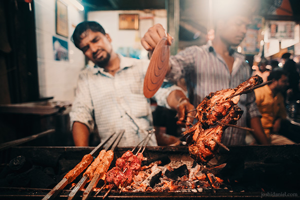 A street food cook grilling meat on Mohammad Ali Road, Mumbai, India