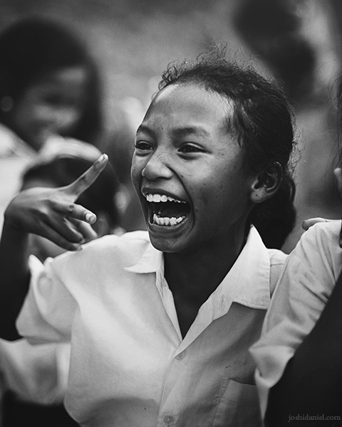 Black and white portrait of a smiling young girl at Taman Bacaan Pelangi (Rainbow Reading Gardens) in Melo Village in Flores, Indonesia