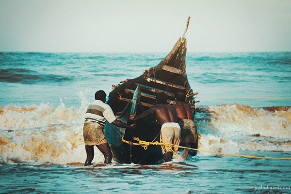A group of fishermen pushing out a boat at Shankhumugham beach in Trivandrum, Kerala, India