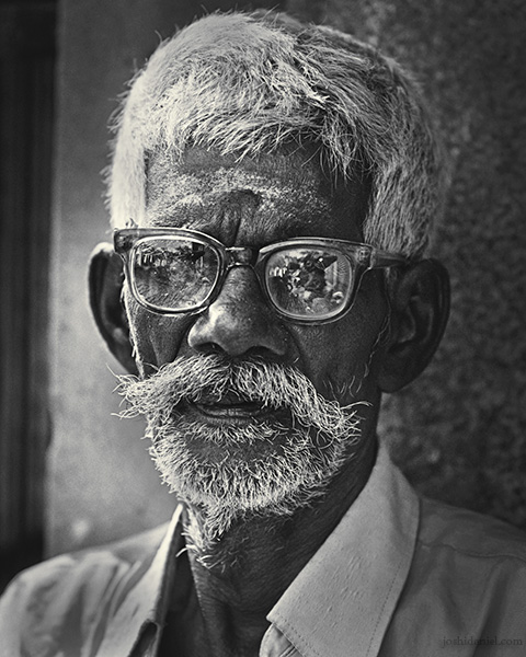 Black and white portrait of an old man from Mylapore wearing spectacles