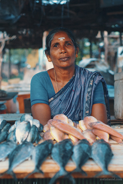 Portrait of a smiling fishmonger lady with the fish laid out in front her at Besant Nagar beach in Chennai, India