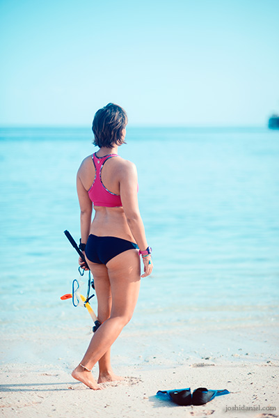 Professional surfer and video maker Gemala Hanafiah standing at the shores of Pink Beach, Indonesia