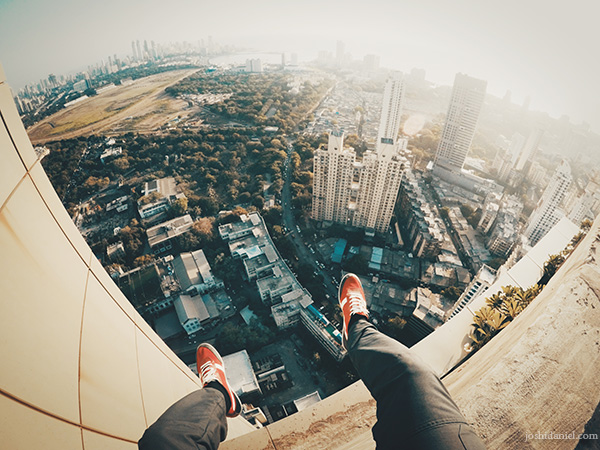 GoPro shot of joshi daniel's feet dangling above the cityscape of South Mumbai, Maharashtra, India