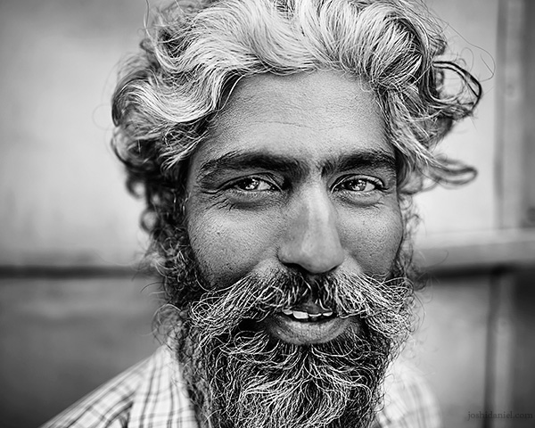 A 28mm wide angle black and white portrait of a smiling man with beard