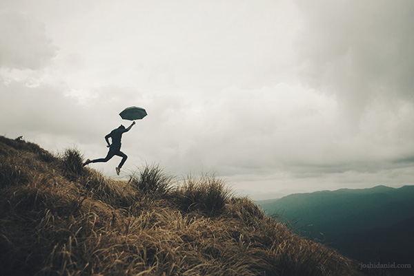 Abilash Thankan leaping with an umbrella in his hand in Ponmudi, Trivandrum, Kerala