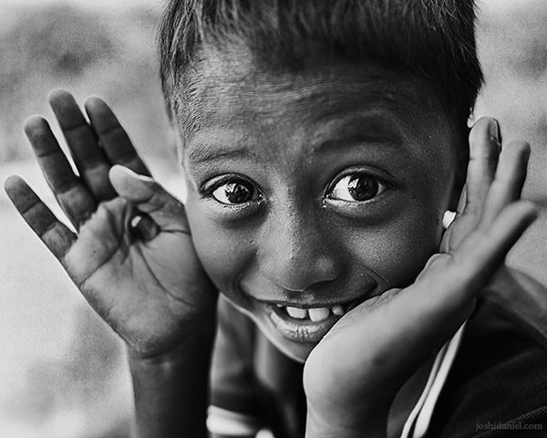 A 28mm wide angle black and white portrait of a smiling boy from Rainbow Village, Tual, Maluku, Indonesia