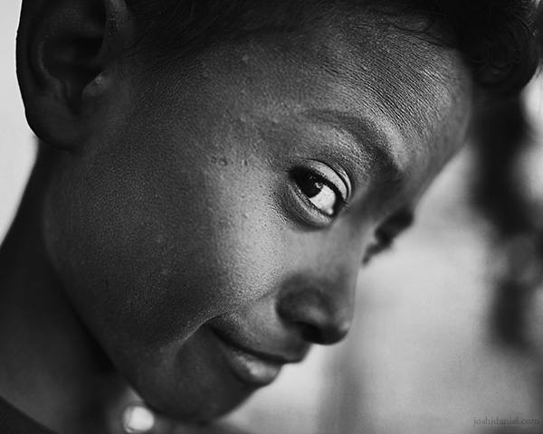 28mm wide angle black and white portrait of a smiling boy from Rainbow Village, Tual, Maluku, Indonesia